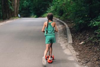 Vue arrière d'une fille trottinette sur une route droite