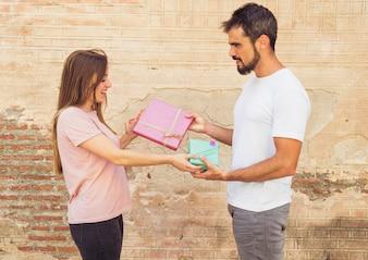 Vue de côté, de, jeune homme, et, femme, donner, cadeau valentin, à, mutuellement