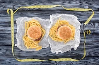 Vue de dessus de deux hamburgers avec frites et ruban à mesurer sur la table en bois