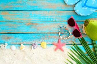 Vue de dessus de sable de plage avec pantoufle, noix de coco, lunettes de soleil, étoile de mer, coquillages