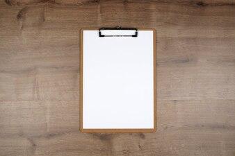 Vue de dessus du presse-papiers avec feuille blanche sur fond de bois marron