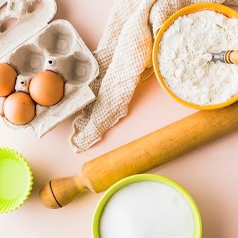 Vue élevée de la farine; Oeuf; sucre et rouleau à pâtisserie sur fond coloré
