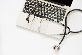Vue élevée, de, stéthoscope, et, lunettes, sur, a, ordinateur portable ouvert, sur, fond blanc