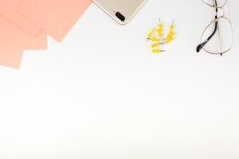 Vue élevée des notes adhésives; téléphone intelligent; des punaises et des lunettes en haut du fond blanc