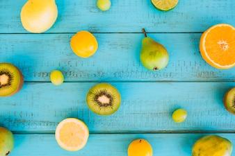 Vue en angle élevé des prunes; poire; grain de raisin; kiwis et agrumes sur planche de bois bleue