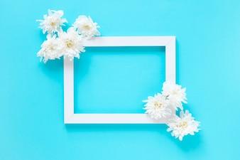 Vue grand angle de fleurs blanches et cadre d'image vide sur fond bleu