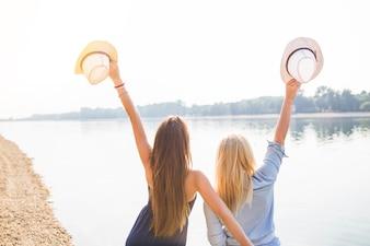 Vue postérieure, de, femmes, debout, près, les, lac, tenue, chapeau