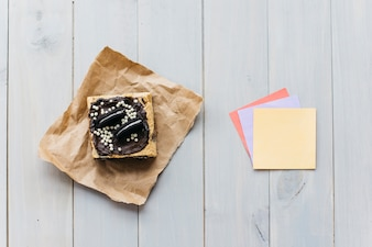 Vue surélevée de la pâtisserie près de notes autocollantes colorées sur fond en bois