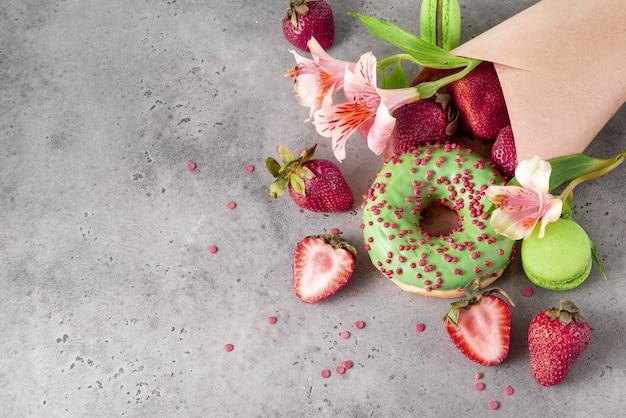 1 ciambella con glassa verde e codette rosse, fragole fresche, amaretto verde, fiori di alstroemeria bordeaux in una busta su una superficie grigia vista dall'alto