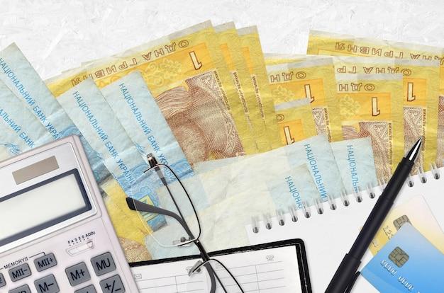 1 banconote in grivna ucraina e calcolatrice con occhiali e penna