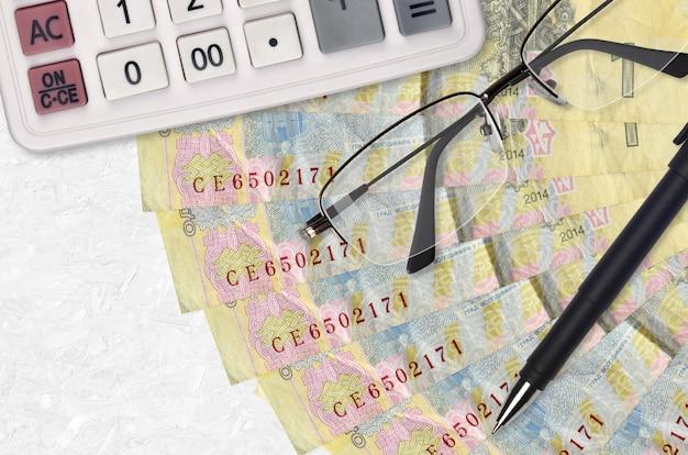 1 grivna ucraina fattura un ventilatore e una calcolatrice con occhiali e penna. prestito aziendale o concetto di stagione di pagamento delle tasse