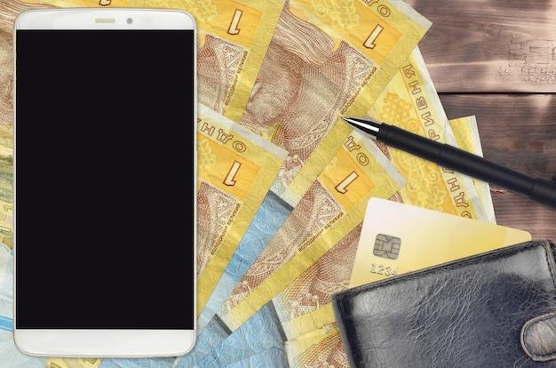 1 banconote in grivna ucraina e smartphone con borsa e carta di credito