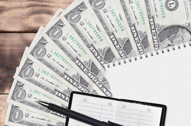 1 ventaglio per banconote da un dollaro usa e blocco note con rubrica e penna nera. concetto di pianificazione finanziaria e strategia aziendale. contabilità e investimenti