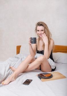 1 giovane donna europea bianca seduta a letto facendo colazione, bevendo da una tazza,