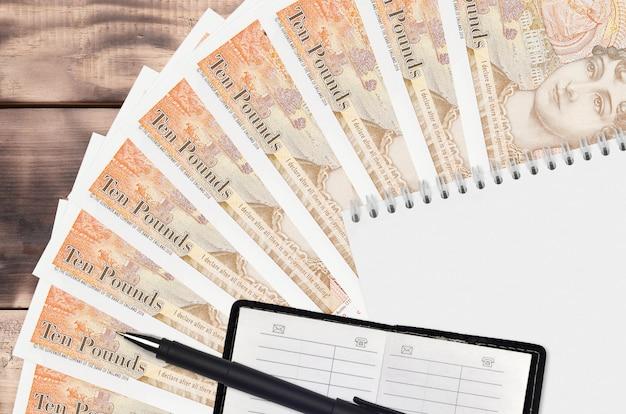 Ventaglio da 10 sterline inglesi e blocco note con rubrica e penna nera. concetto di pianificazione finanziaria e strategia aziendale