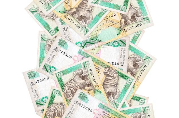 10 banconote in rupie dello sri lanka che volano giù isolate su bianco. molte banconote che cadono con lo spazio bianco della copia sul lato sinistro e destro