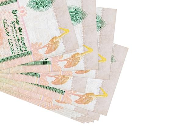 10 banconote in rupie dello sri lanka si trovano in un piccolo mazzo o pacchetto isolato su bianco. concetto di cambio valuta e affari