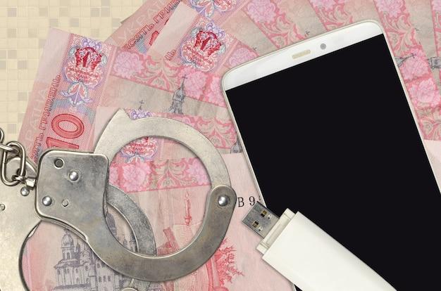10 fatture in grivnia ucraina e smartphone con le manette della polizia. concetto di hacker attacchi di phishing, truffa illegale o distribuzione software di malware