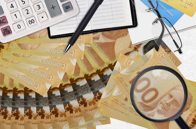 100 dollari canadesi fatture e calcolatrice con occhiali e penna. concetto di stagione di pagamento delle tasse o soluzioni di investimento.