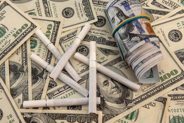 Banconota da 100 dollari con sigarette di tabacco, stili di vita di pericolo