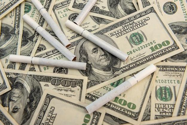 Banconota da 100 dollari con sigarette di tabacco, stili di vita di pericolo Foto Premium