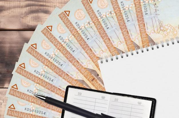 Ventaglio da 100 banconote in pesos dominicani e blocco note con rubrica e penna nera