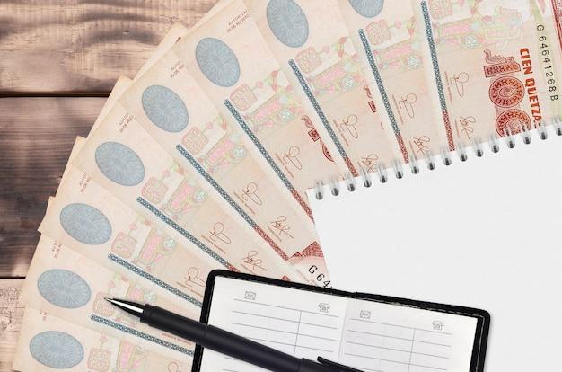 Ventaglio di banconote da 100 quetzales guatemalteche e blocco note con rubrica e penna nera. concetto di pianificazione finanziaria e strategia aziendale