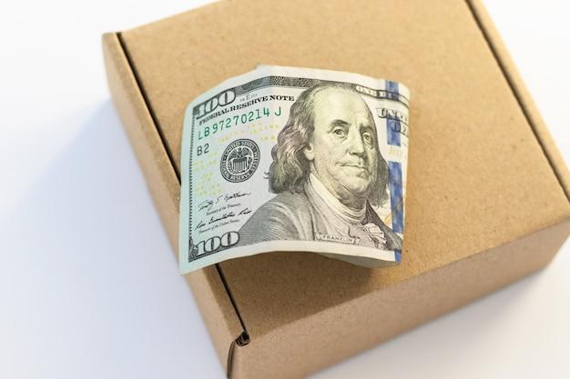 100 centinaia di dollari su scatola di cartone. costo di consegna. denaro e concetto finanziario.