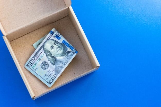 100 dollari usa in scatola di cartone. valuta americana. contanti di carta. costo e spese di consegna. denaro e concetto finanziario. vista dall'alto, piatto, sfondo blu.