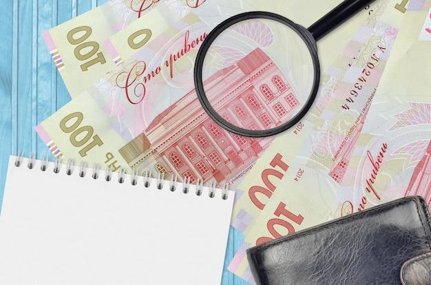 100 banconote hryvnias ucraine e lente d'ingrandimento con borsa nera