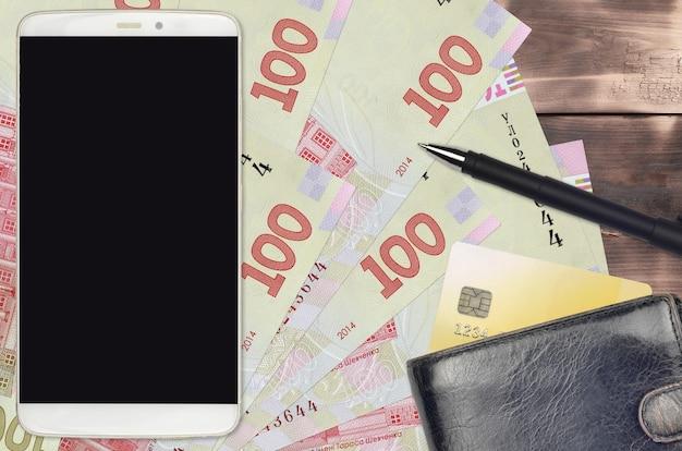 100 banconote hryvnia ucraine e smartphone con borsa e carta di credito
