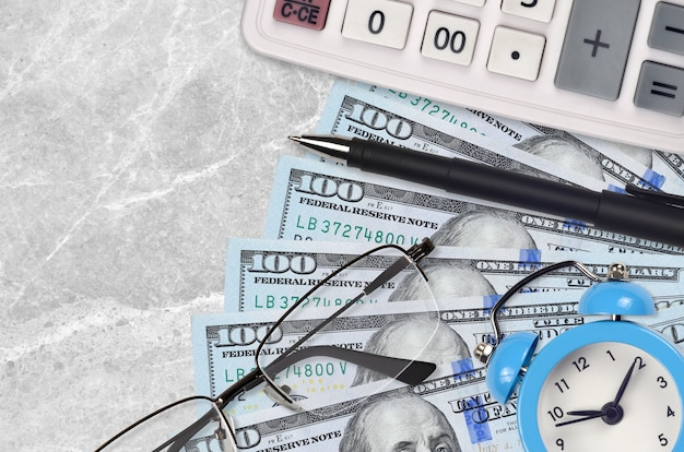100 dollari di bollette e calcolatrice con occhiali e penna
