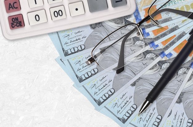 Ventilatore di fatture di 100 dollari usa e calcolatrice con occhiali e penna. prestito aziendale o concetto di stagione di pagamento delle tasse. progetto finanziario