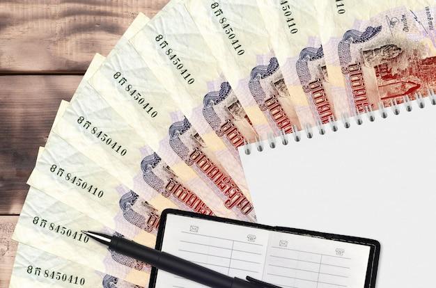Ventaglio di banconote da 1000 riel cambogiani e blocco note con rubrica e penna nera. concetto di pianificazione finanziaria e strategia aziendale