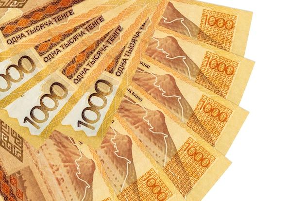 1000 bollette tenge kazako si trova isolato sul muro bianco con copia spazio impilati a forma di ventaglio da vicino. concetto di transazioni finanziarie
