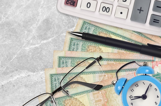 Banconote da 1000 rupie dello sri lanka e calcolatrice con occhiali e sveglia
