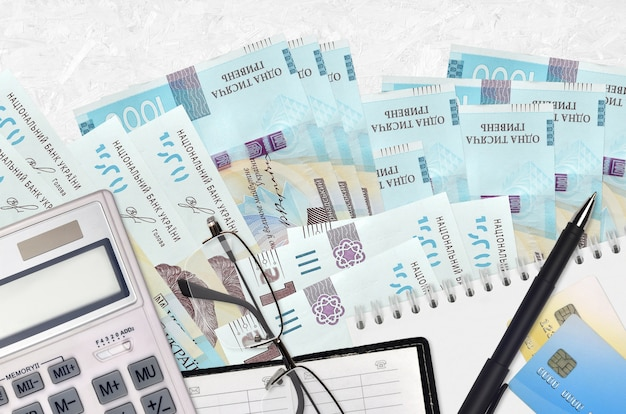 1000 fatture ucraine grivnia e calcolatrice con occhiali e penna. concetto di stagione di pagamento delle tasse o soluzioni di investimento. pianificazione finanziaria o pratiche contabili