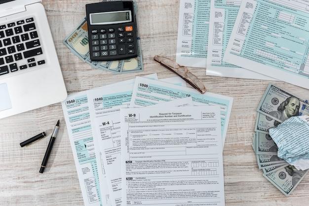 Modulo fiscale 1040 sulla scrivania con calcolatrice a penna e dollaro usa. concetto di business