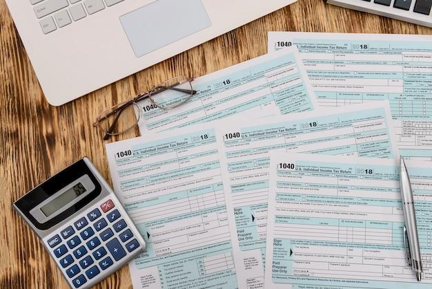 Modulo fiscale 1040 con calcolatrice e laptop