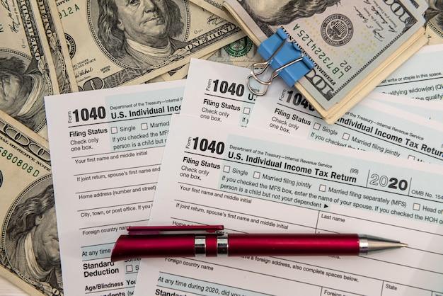 1040 modulo fiscale con penna e banconote in dollari usa, concetto finanziario