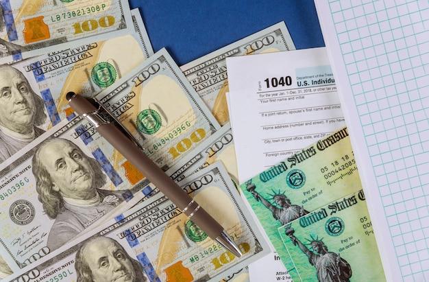 Modulo di dichiarazione dei redditi individuale statunitense 1040 con banconote da cento dollari