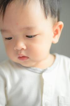 11 mesi di ritratto del neonato, volto di bambino asiatico, ragazzino sorridente
