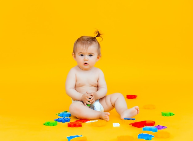 Il bambino di 11 mesi gioca con i giocattoli su uno sfondo giallo. ritratto di un bambino isolato su sfondo giallo yellow