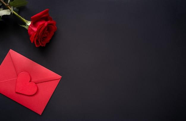 14 san valentino sfondo. fiori rossi di rosa e avvolgono con cuore su sfondo nero, vista dall'alto, copia dello spazio