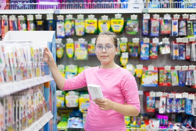 Ragazza di 14 anni in cerca di merce nel reparto ufficio in negozio