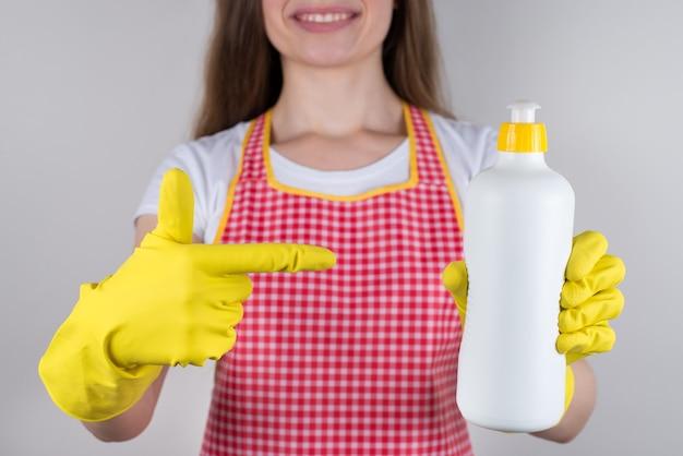 Crema 2 in 1 con glicerina e prodotto chimico liquido per il concetto di piatti. ritagliata ravvicinata di soddisfatto allegro con la moglie di sorriso a trentadue denti che tiene la bottiglia con muro grigio isolato aroma di limone fresco