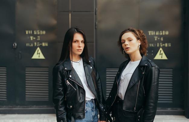 2 bellissime modelle in piedi contro un muro scuro
