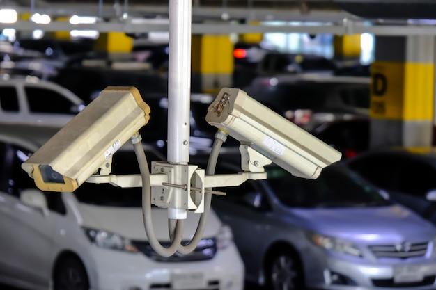 2 cctv o close circuit television sono monitorati e registrano le auto nel parcheggio del centro commerciale