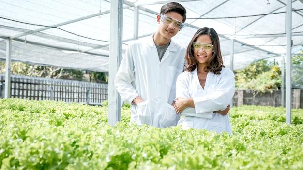 2 gli scienziati stanno in una fattoria idroponica di un contadino che coltivano un'insalata e una lattuga di verdure biologiche.