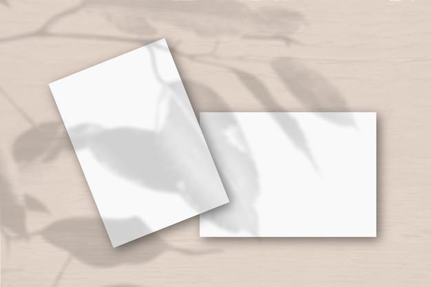 2 fogli di carta ruvida bianca contro un muro color pesca. mockup con una sovrapposizione di ombre di piante. la luce naturale proietta le ombre di una pianta esotica. disposizione piana, vista dall'alto. orientamento orizzontale.